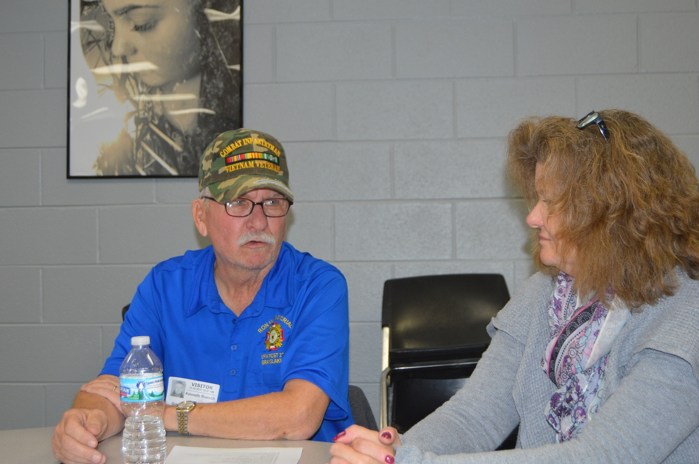 Ken Ruesch, Retired USA, Lt.Col talks with one of the teachers at the Grayslake North Veterans Day Program.